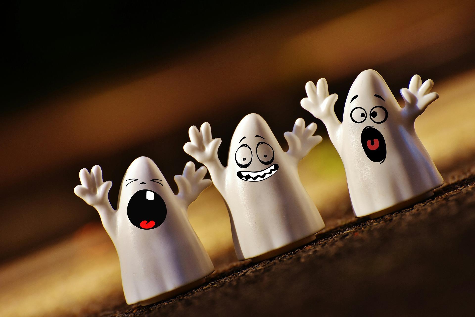 Tre piccoli fantasmi in plastica sul tavolo